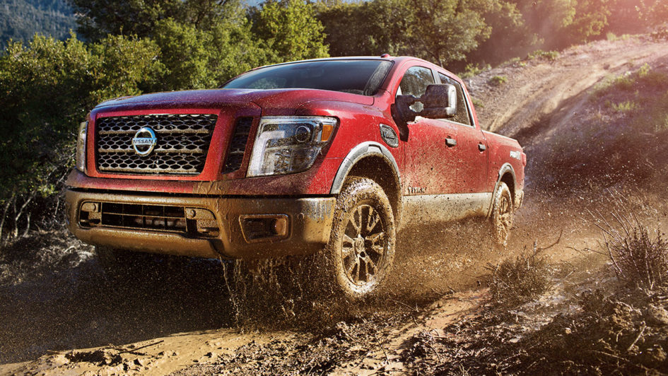 A red 2017 Nissan TITAN truck driving off road.