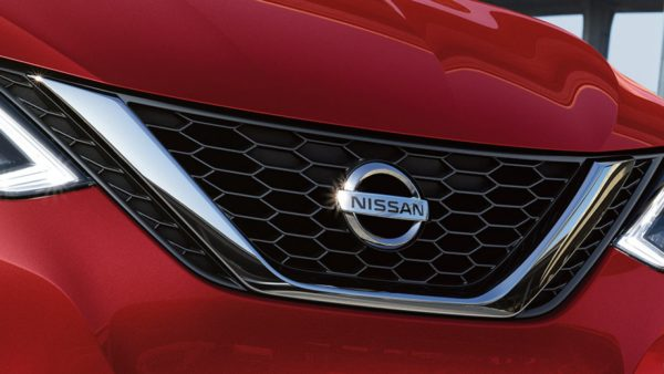 A red Nissan car with the Nissan logo on the grille.