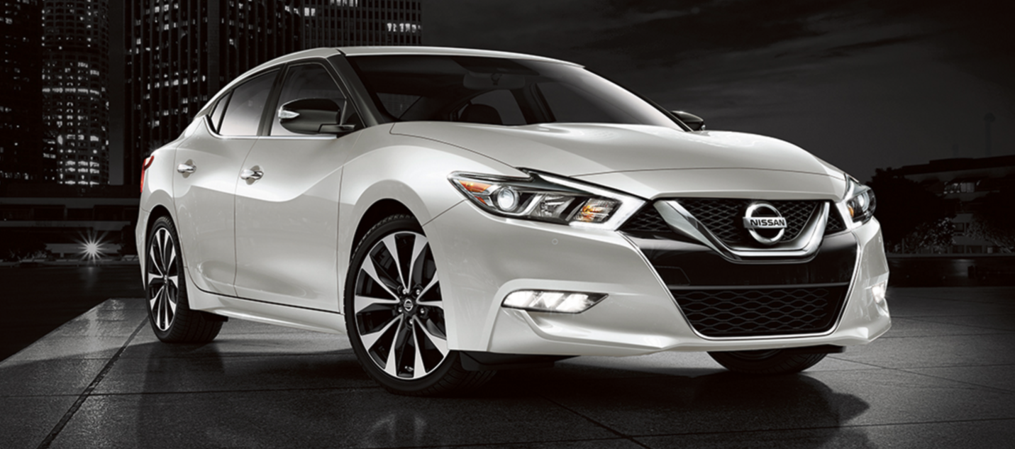 A white 2017 Nissan Maxima parked outside the city at night.