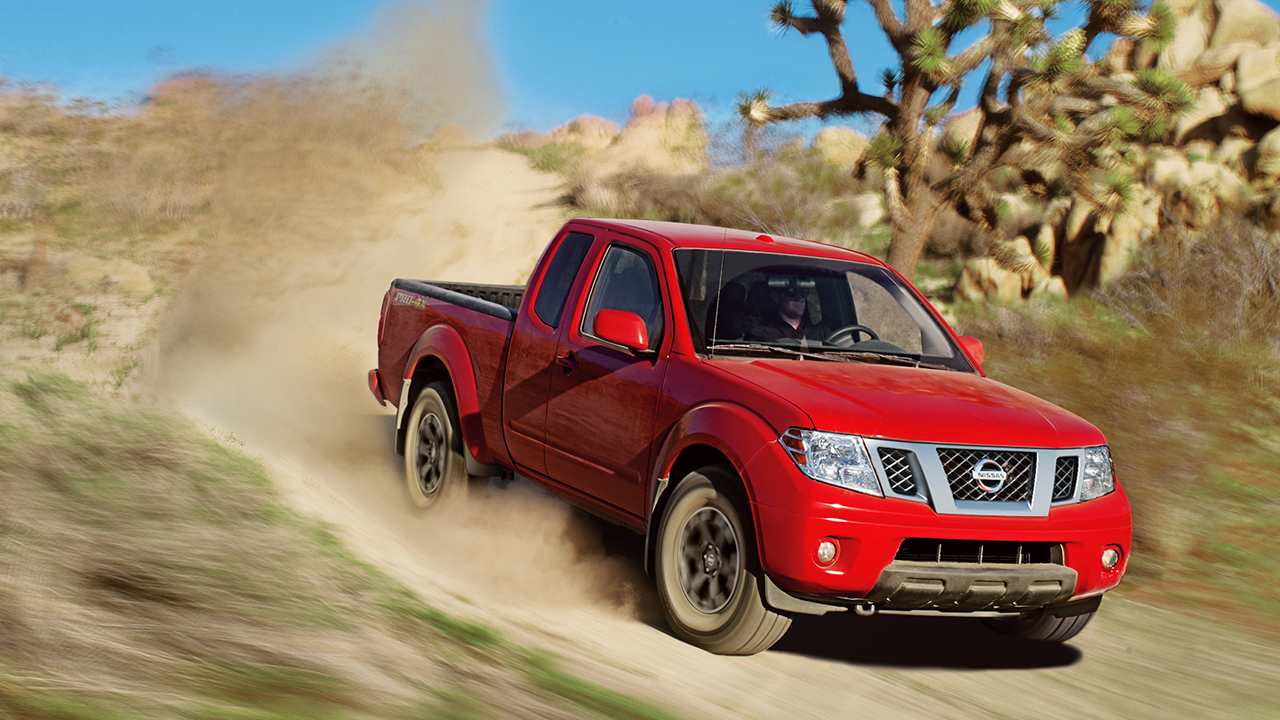 A red 2017 Nissan Frontier driving down a dirt road in the desert.