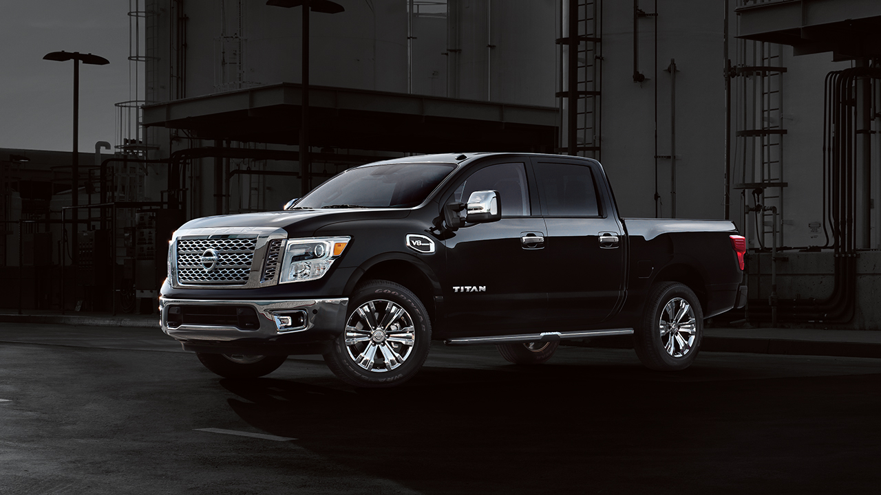 A black 2017 Nissan Titan parked outside a warehouse at night.