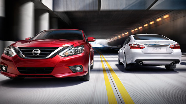 A red 2016 Nissan Altima (front view) and glacier white 2016 Nissan Altima cross paths in a tunnel