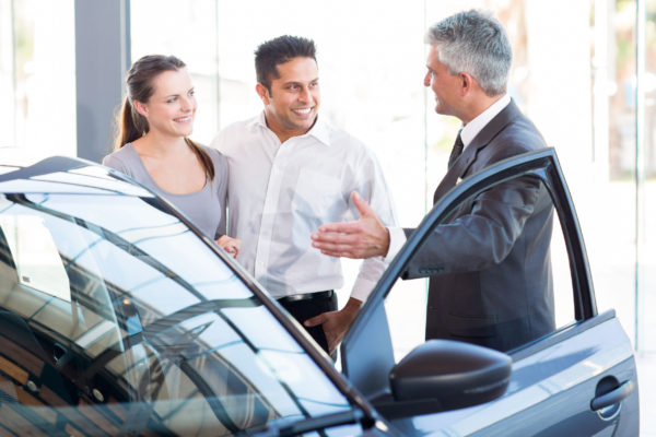 Couple with a Sales Person at Asheboro Nissan Dealer