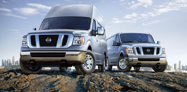 Two Nissan NV Cargo commercial vehicles on a dirt road.