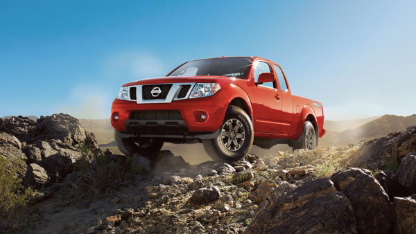 A red 2017 Nissan Frontier driving over rocks on a trail.