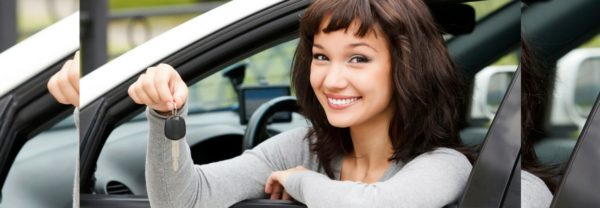 A woman in a car holding the keys, in a blog post about used Nissan cars.